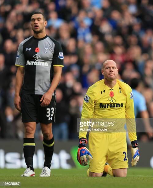 Brad Friedel of Tottenham Hotspur and teammate Steven Caulker react after Sergio Aguero scored the winning goal during the Barclays Premier League...