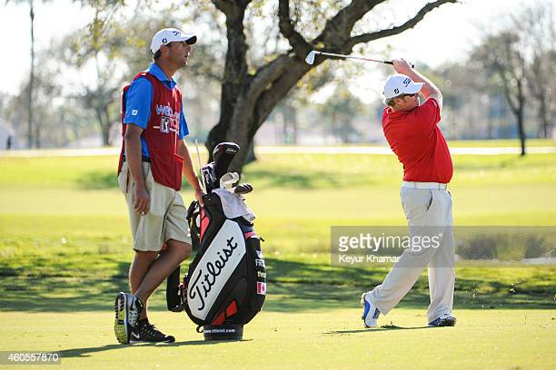 Brad Fritsch of Canada plays an iron from the first hole fairway while his caddie stands with his Titleist bag on the Champion Course during the...