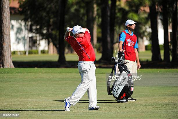 Brad Fritsch of Canada plays an iron from the third hole fairway as his caddie stands with his Titleist bag on the Champion Course during the sixth...