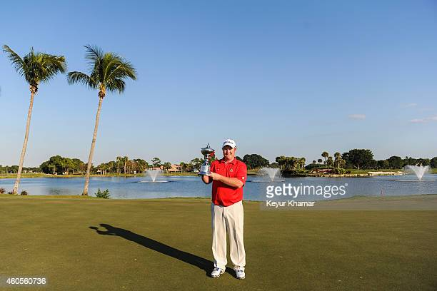 Brad Fritsch of Canada smiles with the Championship trophy on the 18th hole green of the Champion Course following his sevenstroke victory in the...