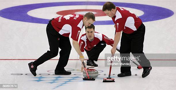 Brad Gushue of Canada releases the stone flanked by his teammates Mark Nichols and Mike Adam during the preliminary round of the men's curling...