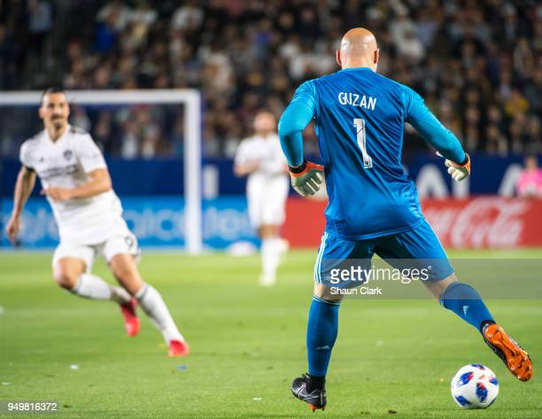 Brad Guzan of Atlanta United passes the ball as Zlatan Ibrahimovic of Los Angeles Galaxyc charges in during the Los Angeles Galaxy's MLS match...
