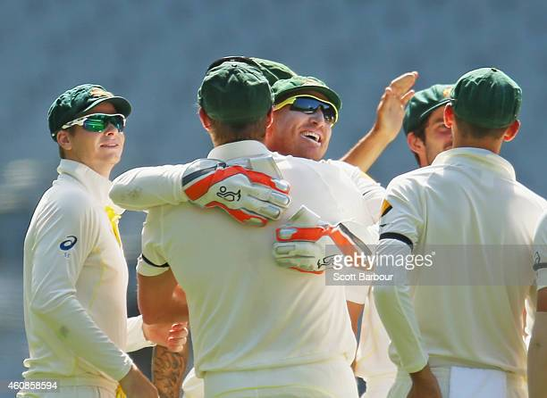 Brad Haddin of Australia is congratulated by team mates after taking a catch to dismiss Cheteshwar Pujara of India off the bowling of Ryan Harris...