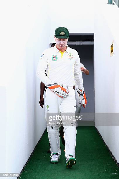 Brad Haddin of Australia returns to the ground after the lunch break still nursing his shoulder after landing heavily while wicketkeeping during Day...