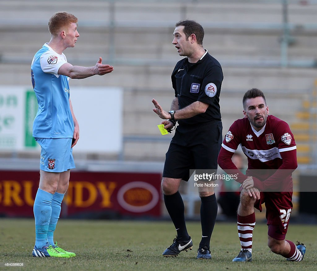 Brad Halliday of York City pleads his innocence as referee Jeremy Simpson prepares to show him a yellow card for a foul on Ricky Holmes of Northampton Town during the Sky Bet League Two match between Northampton Town and York City at Sixfields Stadium on February 21, 2015 in Northampton, England.