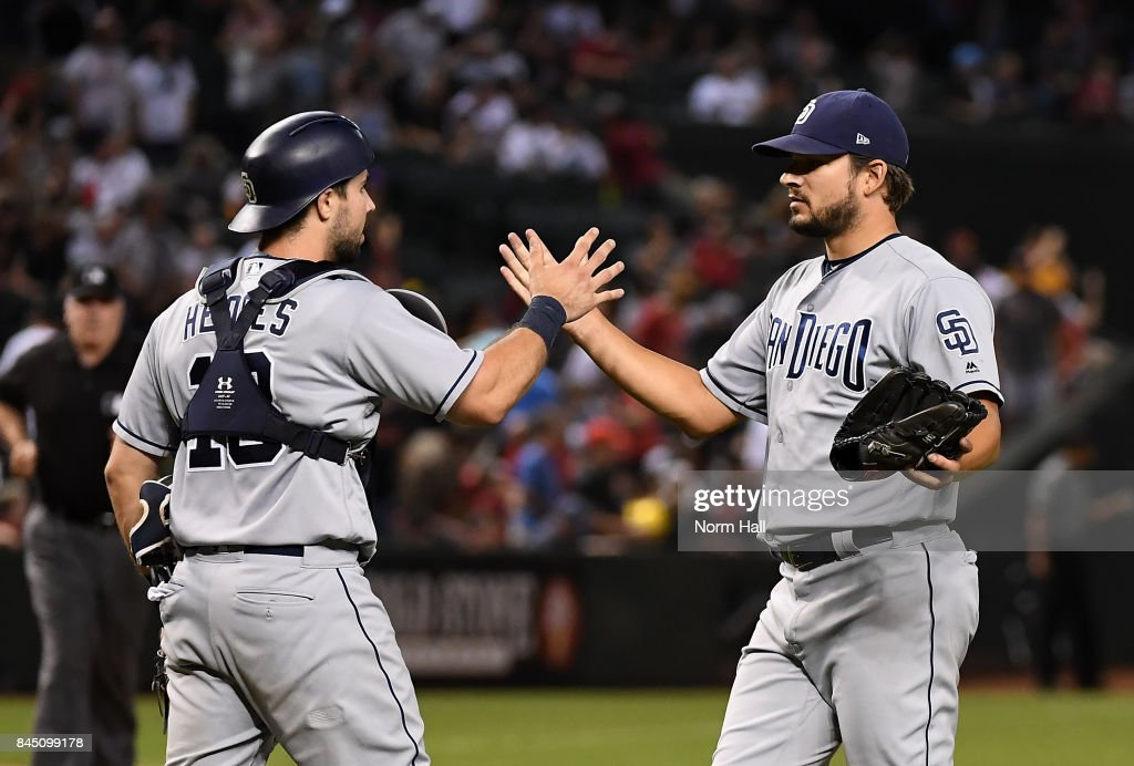 Brad Hand #52 of the San Diego Padres and teammate Austin Hedges #18 celebrate an 8-7 win against the Arizona Diamondbacks at Chase Field on September 9, 2017 in Phoenix, Arizona.