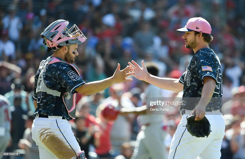 Brad Hand #52 of the San Diego Padres, right, is congratulated by Raffy Lopez #0 after getting the final out in the ninth inning of a baseball game against the St. Louis Cardinals at PETCO Park on May 13, 2018 in San Diego. The Padres won 5-3.