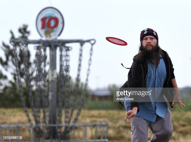 Brad Henderson throws at basket on the Village Greens Disc Golf course August 03 2018 Henderson and a friend shot a round of disc golf after a long...