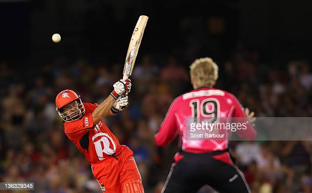 Brad Hodge of the Renegades bats as Steve Smith of the Sixers looks on in the field during the T20 Big Bash League match between the Melbourne...
