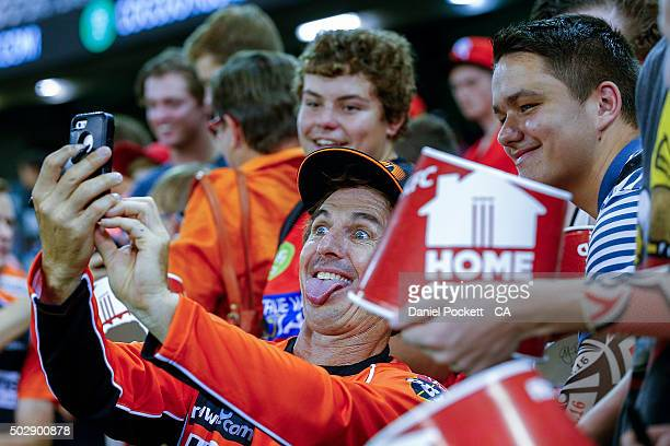 Brad Hogg of Perth Scorchers takes a selfie with fans after the Big Bash League match between the Melbourne Renegades and the Perth Scorchers at...