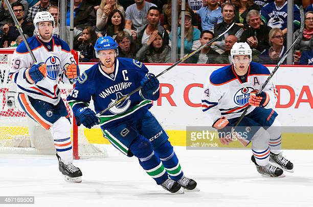 Brad Hunt and Taylor Hall of the Edmonton Oilers and Henrik Sedin of the Vancouver Canucks skate up ice during their NHL game at Rogers Arena October...