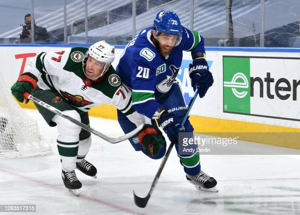 Brad Hunt of the Minnesota Wild and Brandon Sutter of the Vancouver Canucks battle for the puck during the second period of Game One of the Eastern...