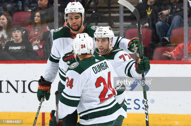 Brad Hunt of the Minnesota Wild is congratulated by teammates Jordan Greenway and Matt Dumba after scoring a goal against the Arizona Coyotes during...