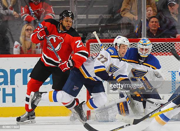 Brad Hunt of the St Louis Blues is bumped by Devante SmithPelly of the New Jersey Devils during the first period at the Prudential Center on December...
