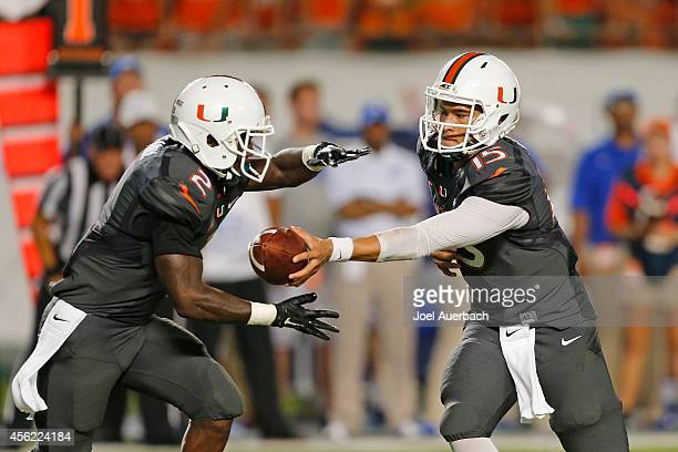 Brad Kaaya hands the ball off to Joseph Yearby of the Miami Hurricanes against the Duke Blue Devils during first quarter action on September 27 2014...