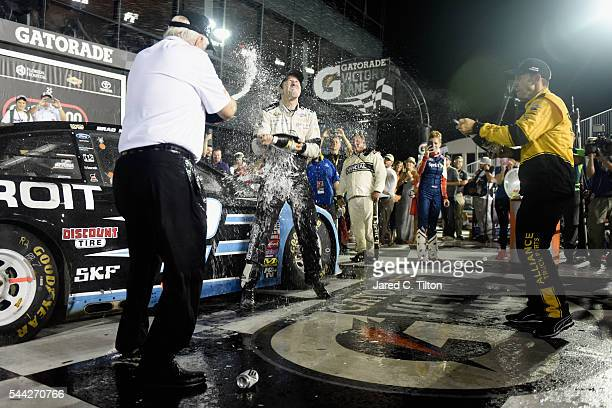 Brad Keselowsk driver of the Detroit Genuine Parts Ford celebrates with champagne in Victory Lane with team owner Roger Penske and crew chief Paul...