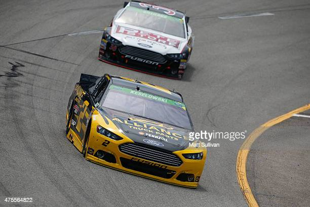 Brad Keselowski, driver of the Alliance Truck Parts Ford, races with David Gilliland, driver of the The Pete Store Ford, during the NASCAR Sprint Cup...