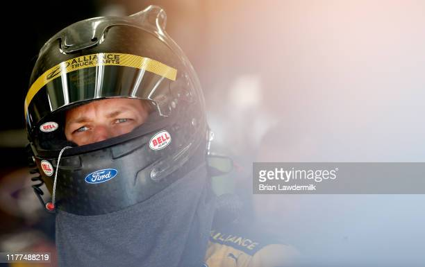 Brad Keselowski driver of the Alliance Truck Parts Ford stands in the garage area during practice for the Monster Energy NASCAR Cup Series Bank of...