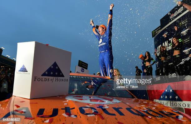 Brad Keselowski driver of the Autotrader Ford celebrates in Victory Lane after winning the Monster Energy NASCAR Cup Series Folds Of Honor QuikTrip...