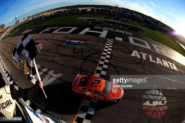 Brad Keselowski driver of the Autotrader Ford crosses the finish line to win the Monster Energy NASCAR Cup Series Folds of Honor QuikTrip 500 at...