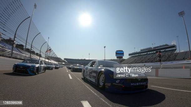Brad Keselowski, driver of the Dent Wizard Ford, and Martin Truex Jr., driver of the Auto-Owners Insurance Toyota, lead the field on a pace lap prior...
