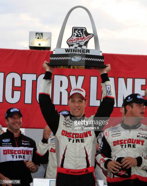 Brad Keselowski driver of the Discount Tire Dodge hold up the trophy after winning the NASCAR 5hour Energy 250 at Gateway International Raceway on...