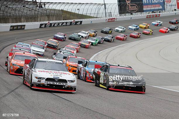 Brad Keselowski driver of the Discount Tire Ford and Erik Jones driver of the GameStop/Call of Duty Toyota lead the field at the start of the NASCAR...