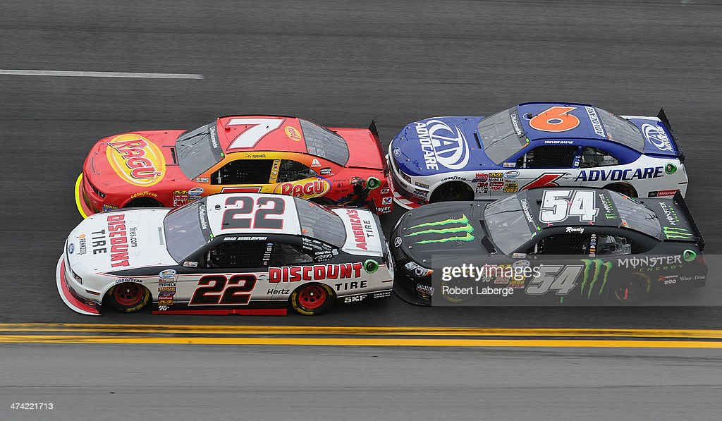 Brad Keselowski, driver of the #22 Discount Tire Ford, and Regan Smith, driver of the #7 Ragu Chevrolet, race ahead of Kyle Busch, driver of the #54 Monster Energy Toyota, and Trevor Bayne, driver of the #6 Advocare Ford, on the last lap of the NASCAR Nationwide Series DRIVE4COPD 300 at Daytona International Speedway on February 22, 2014 in Daytona Beach, Florida.