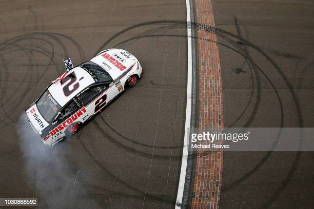 Brad Keselowski driver of the Discount Tire Ford celebrates with a burnout after winning the Monster Energy NASCAR Cup Series Big Machine Vodka 400...