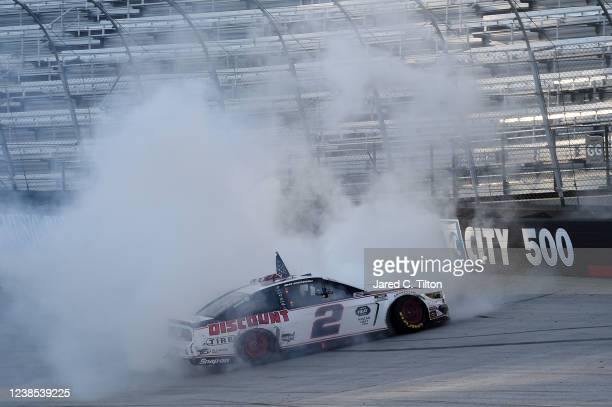 Brad Keselowski, driver of the Discount Tire Ford, celebrates with a burn out after winning the NASCAR Cup Series Food City presents the Supermarket...