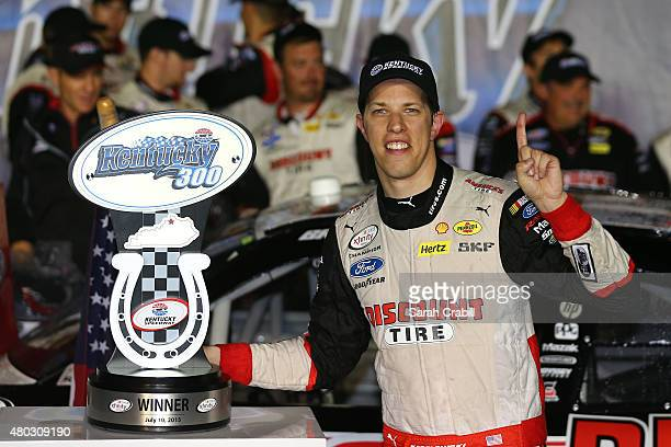 Brad Keselowski driver of the Discount Tire Ford poses with the winner's trophy in Victory Lane after winning the NASCAR XFINITY Series Kentucky 300...