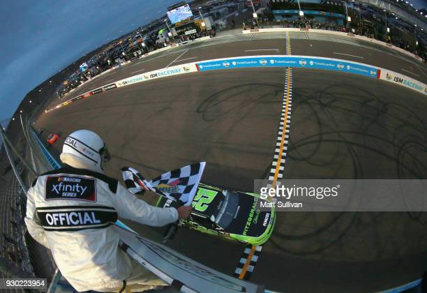 Brad Keselowski driver of the Fitzgerald Glider Kits Ford takes the checkered flag to win the NASCAR Xfinity Series DC Solar 200 at ISM Raceway on...