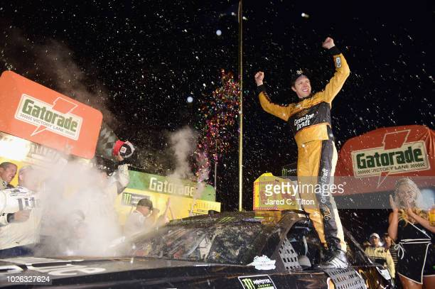Brad Keselowski driver of the Miller Genuine Draft Ford celebrates in Victory Lane after winning the Monster Energy NASCAR Cup Series Bojangles'...