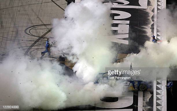 Brad Keselowski driver of the Miller Lite Dodge celebrates with a burnout after winning the NASCAR Sprint Cup Series Irwin Tools Night Race at...