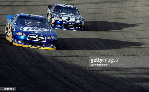 Brad Keselowski driver of the Miller Lite Dodge drives alongside Jimmie Johnson driver of the Lowe's Chevrolet during the NASCAR Sprint Cup Series...
