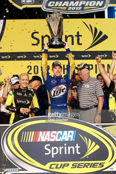 Brad Keselowski driver of the Miller Lite Dodge hoist the series trophy in Champions Victory Lane after winning the series championship and finishing...