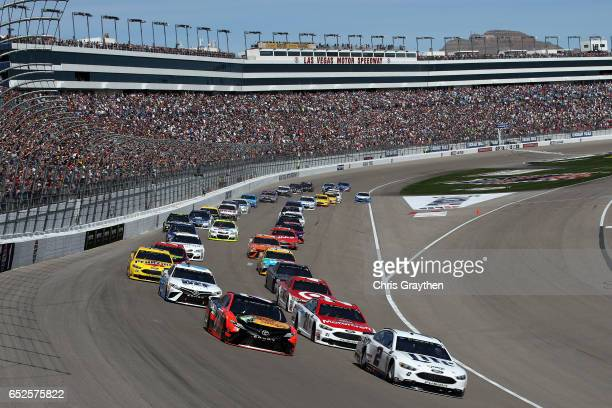 Brad Keselowski driver of the Miller Lite Ford and Martin Truex Jr driver of the Bass Pro Shops/TRACKER BOATS Toyota lead the field into turn one to...