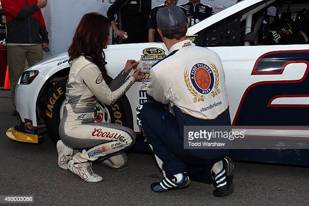 Brad Keselowski driver of the Miller Lite Ford and Miss Coors Light Amanda Mertz place the Coors Light Pole Award decal on his car after qualifying...