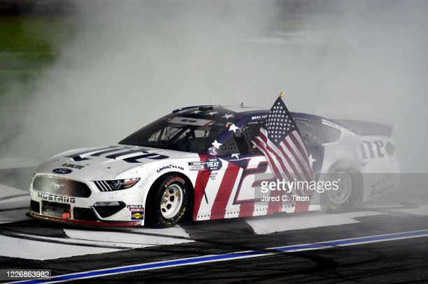 Brad Keselowski driver of the Miller Lite Ford celebrates with a burnout after winning the NASCAR Cup Series CocaCola 600 at Charlotte Motor Speedway...