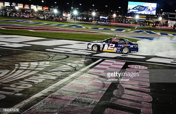 Brad Keselowski driver of the Miller Lite Ford celebrates with a burnout after winning during the NASCAR Sprint Cup Series Bank of America 500 at...