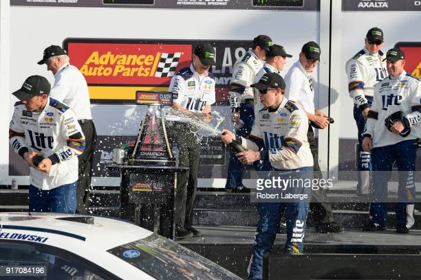 Brad Keselowski driver of the Miller Lite Ford celebrates with champagne in Victory Lane after winning the Monster Energy NASCAR Cup Series Advance...