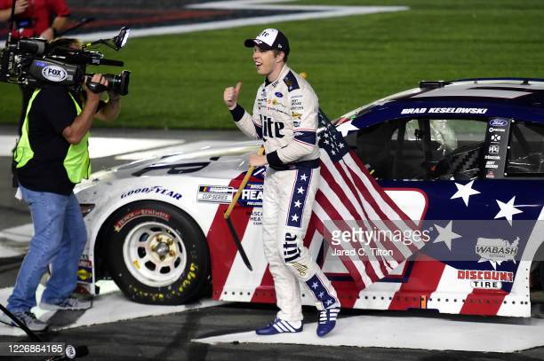 Brad Keselowski driver of the Miller Lite Ford celebrates with the American flag after winning the NASCAR Cup Series CocaCola 600 at Charlotte Motor...