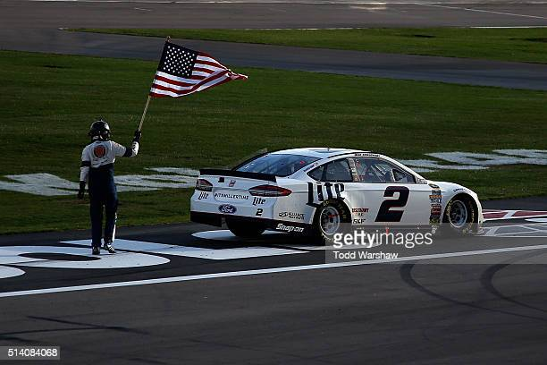 Brad Keselowski driver of the Miller Lite Ford celebrates with the American Flag after winning the NASCAR Sprint Cup Series Kobalt 400 at Las Vegas...