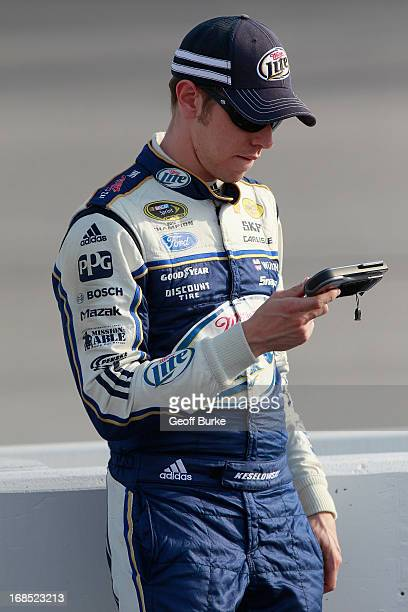 Brad Keselowski driver of the Miller Lite Ford checks results while standing on pit road during qualifying for the NASCAR Sprint Cup Series...
