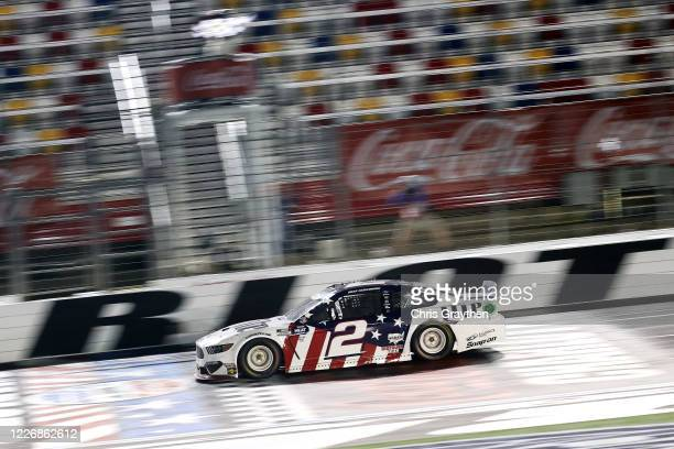 Brad Keselowski, driver of the Miller Lite Ford, crosses the finish line to win the NASCAR Cup Series Coca-Cola 600 at Charlotte Motor Speedway on...