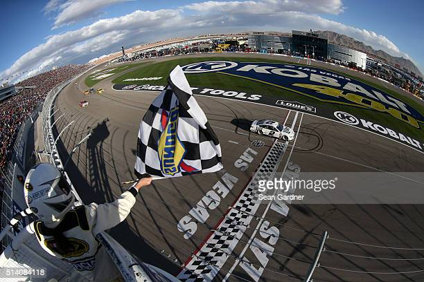 Brad Keselowski driver of the Miller Lite Ford crosses the finish line to win the NASCAR Sprint Cup Series Kobalt 400 at Las Vegas Motor Speedway on...
