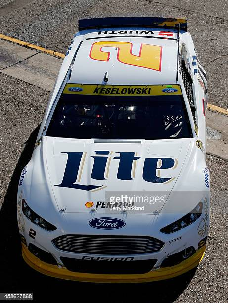 Brad Keselowski driver of the Miller Lite Ford drives through the garage area during practice for the NASCAR Sprint Cup Series Quicken Loans 500 at...