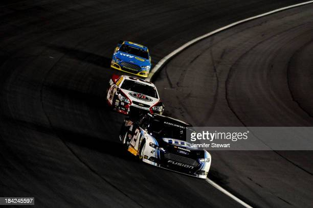 Brad Keselowski driver of the Miller Lite Ford leads Kevin Harvick driver of the Jimmy John's Chevrolet and Ricky Stenhouse Jr driver of the My Best...