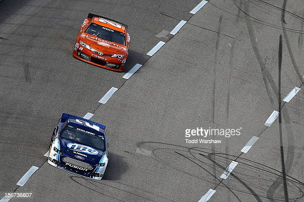 """Brad Keselowski, driver of the Miller Lite Ford, leads Matt Kenseth, driver of the Home Depot """"Let's Do This"""" Toyota, during the NASCAR Sprint Cup..."""