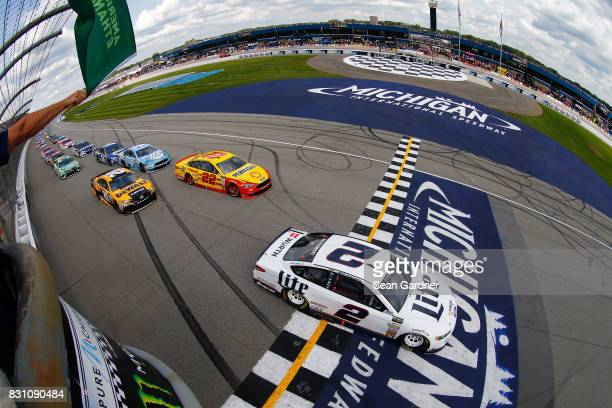 Brad Keselowski driver of the Miller Lite Ford leads the field past the green flag to start the Monster Energy NASCAR Cup Series Pure Michigan 400 at...